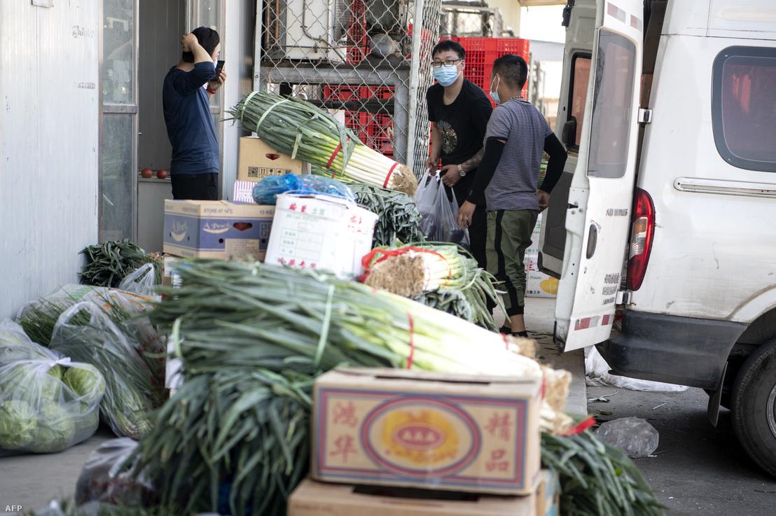 Munkavállalók zöldségeket rendeznek a zárt Hszinfadi piacon, 2020. június 14-én.