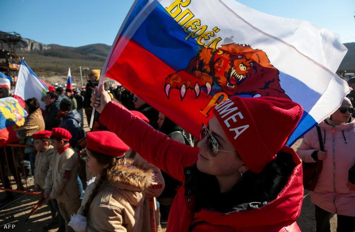 Krím feliratos sapkában, orosz zászlóval ünnepli egy nő a félsziget annektálását Szevasztopolban 2020. március 18-án