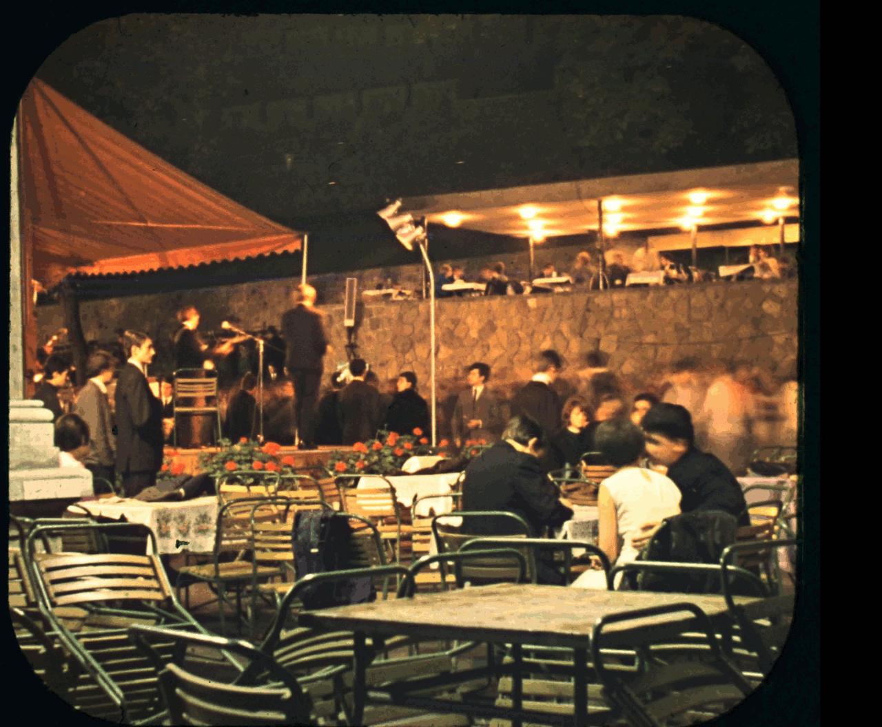 Csendes, iszogatós este az Ifiparkban (Várkert Bazár) élő zenével. Korán van még, sok az üres asztal és szék.