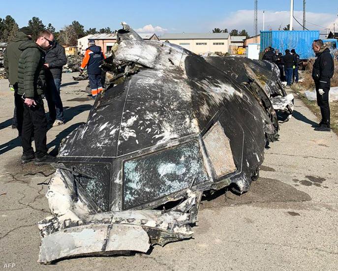 Emberek állnak az Iránban lelőtt ukrán utasszállító roncsdarabjánál Teherán közelében 2020. január 8-án