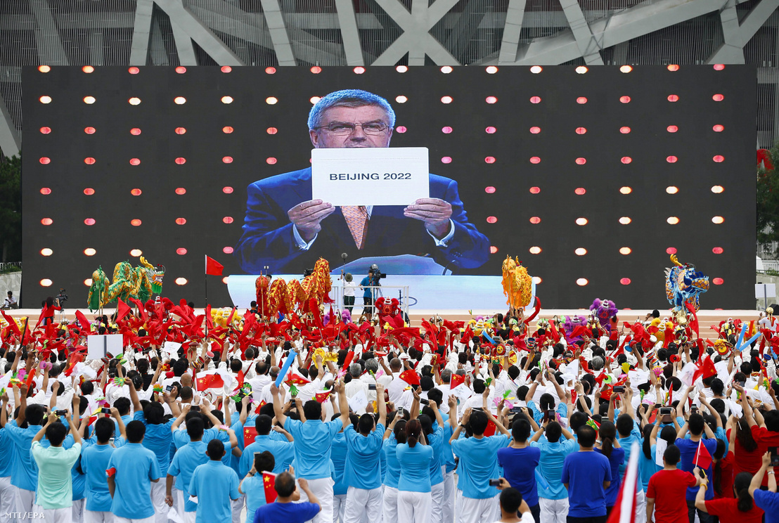 A pekingi Olimpiai Parkban ünnepelnek az emberek, az óriáskivetítőn Thomas Bach, a Nemzetközi Olimpiai Bizottság elnöke Peking nevét mutatja, miután a NOB 128. kongresszusa a kínai fővárosnak ítélte oda a 2022-es téli olimpia rendezésének jogát Kuala Lumpur-i ülésén 2015. július 31-én.