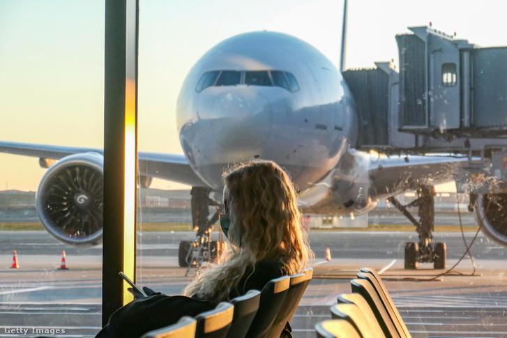 Maszkot viselő utas várakozik az isztambuli repülőtéren 2020. március 18-án.