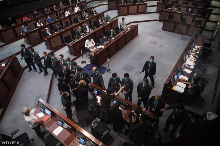 Biztonsági őrök állnak sorfalat az ellenzéki képviselők előtt a hongkongi parlament üléstermében 2020. június 4-én miután a 70 fős hongkongi törvényhozás 41 igen és 1 nem szavazattal elfogadta a kínai himnusz védelmét célzó vitatott törvénytervezetet. A jogszabály szerint három év szabadságvesztéssel és 50 ezer hongkongi dollárig lenne büntethető aki kigúnyolja vagy meggyalázza a kínai himnuszt.