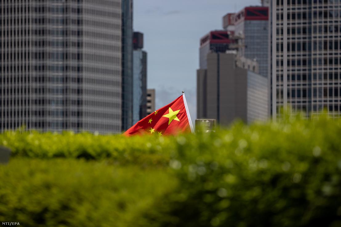 Kínát támogató tüntetők vonulnak egy nemzeti színű zászlóval Hongkongban 2020. június 30-án