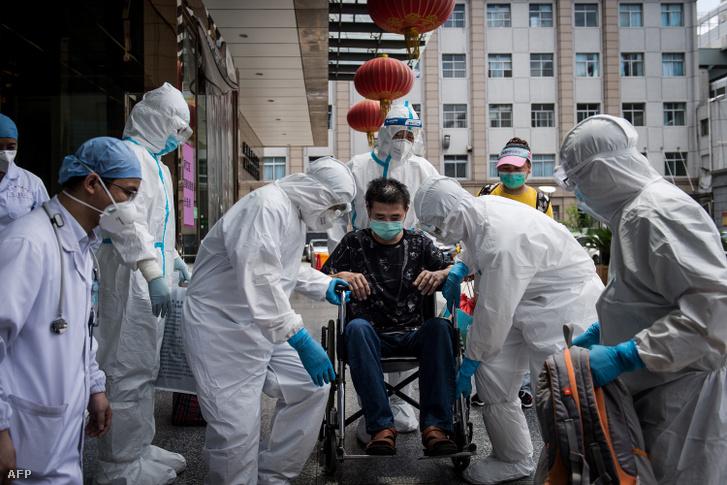 Egészségügyi dolgozók segítik az utolsó koronavírus-fertőzésből gyógyult beteget Wuhanban 2020. június 17-én