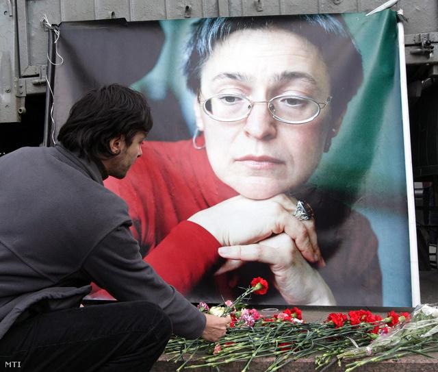 Az emberjogi aktivista Anna Politkovszkaja orosz újságíró portréja előtt virágot helyez el egy megemlékező Moszkvában 2009. október 7-én, a publicista meggyilkolásának harmadik évfordulóján.