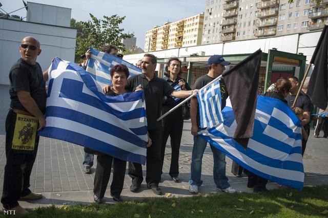 Ellentüntetők zászlókat lengetnek Mustafa Kemal Atatürk Emlékpark szoboravatási ünnepségén.