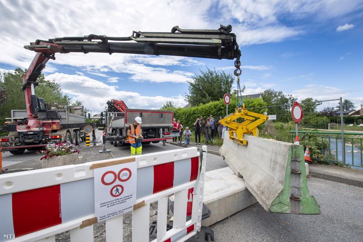 A 2020. június 30-án közreadott képen daru távolítja el a betontömböket a francia határ melletti svájci Thonexben június 14-én