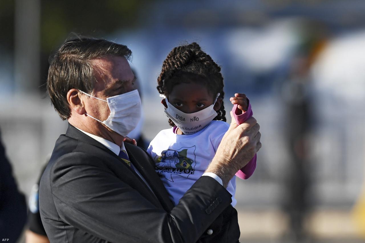 Május 12.A maszkos Bolsonaro egy kislányt tart a kezében egy zászlófelvonáson.