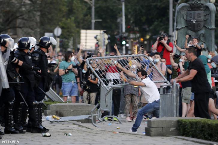 Rendőrökre dobálnak tárgyakat tüntetők a parlament épületénél Belgrádban 2020. július 8-án. A tüntetők a koronavírus-járvány miatt tervezett újabb korlátozó intézkedések ellen tiltakoztak.