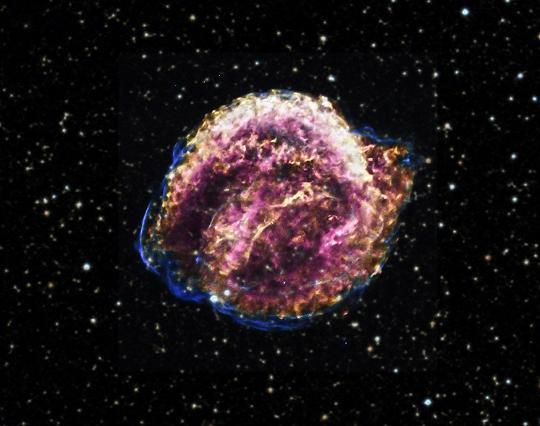 Az 1604-es Kepler-féle szupernóva-maradvány röntgenképe a Chandra műhold adatai alapján. A kisebbtől a nagyobb felé haladva a röntgensugárzás energiáját öt szín kódolja: vörös, sárga, zöld, kék, bíbor. A kép mögé illesztett csillagos háttér a Digitized Sky Survey felmérésből származik.