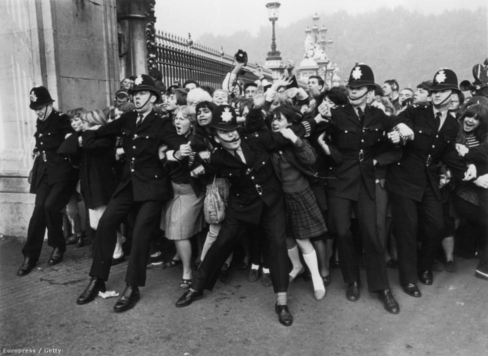 Rendőrök próbálják visszatartani a hisztérikus tömeget a Buckingham Palota kapujában a Beatles lovaggá ütésének napján.