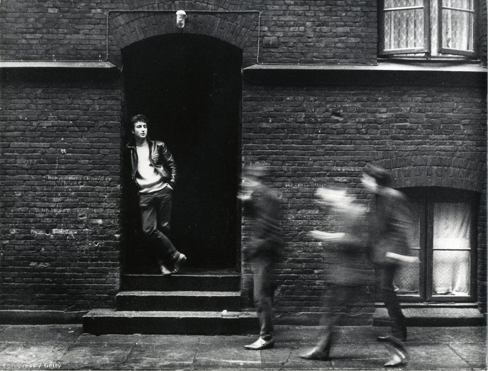 1960-ban John Lennonék a jobb pénzkereseti lehetőségek miatt átköltöztek Hamburgba, ahol már mint The Beatles léptek fel Pete Best dobossal. Ebben az időszakban, de nem itt, hanem Angliában figyelt fel rájuk Brian Epstein menedzser, aki a Stuart Sutcliffe által kitalált bőrdzsekis külsőt lecseréltette a klasszikus, öltönyös-gombafrizurás imidzsre. A kép John Lennont ábrázolja egy hamburgi ajtó előtt 1961-ben.