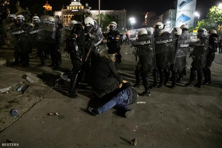 Sérült embert segítenek Belgrádban, a parlament épülete előtt, ahogy kormányellenes tüntetők és rendőrök csaptak össze 2020. július 10-én