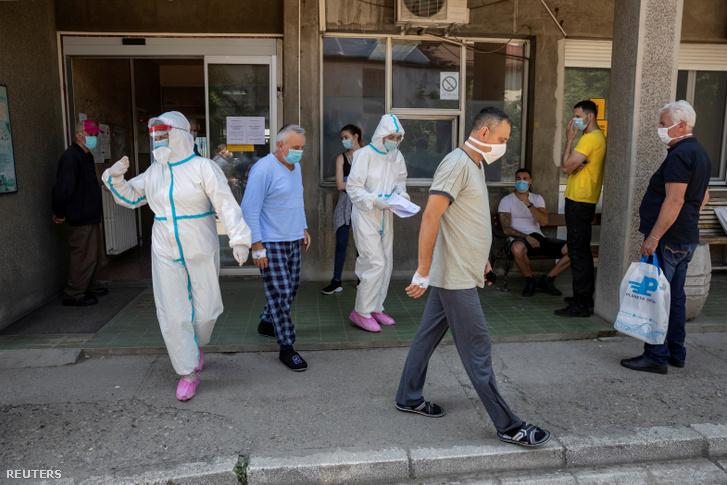 Védőruhás egészségügyi dolgozók és koronavírusos tüneteket mutató betegek a belgrádi Fertőző és Trópusi Betegségek Klinikája előtt 2020. június 26-án