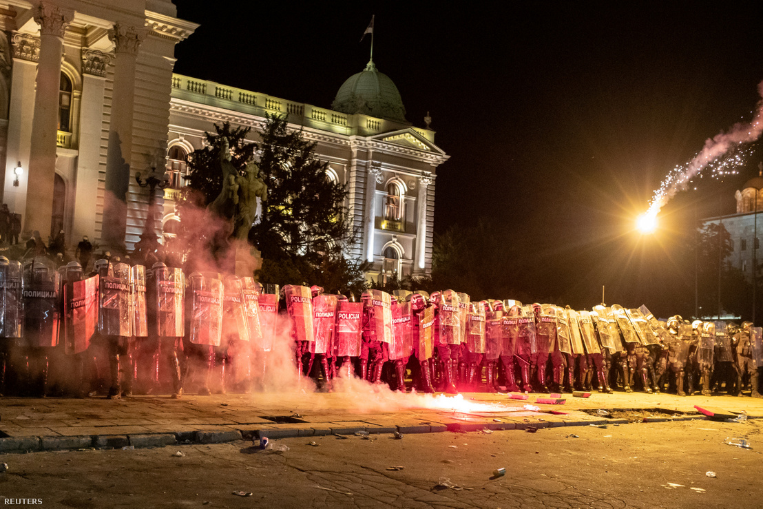 Rohamrendőrök állnak sorfalat a belgrádi parlament épülete előtt 2020. július 10-én, miközben kormányellenes tüntetők fáklyákkal dobálják őket