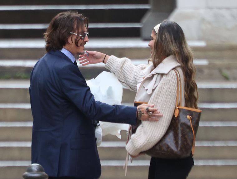A színész ugyanis éppen a bíróság előtt cigizgetett, amikor egy női rajongó jelent meg mellette, kezében egy hatalmas virágcsokorral.