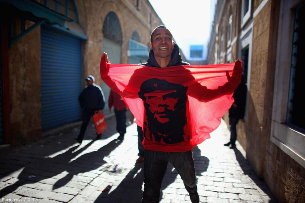 A kép 2011. január 23-án készült Tunéziában. Egy tüntető egy Che Guevarát ábrázoló vörös zászlót lobogtat a tunéziai miniszterelnöki hivatal előtt. A tüntetők a jázmin forradalom idején utaztak fel a fővárosba, ahol letépték a hivatal köré fölhúzott szögesdrótot. A rendőrség és a hadsereg nem tanúsított ellenállást.