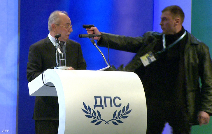 Egy ismeretlen férfi fegyvert fog Ahmed Dogan fejéhez beszéde alatt Szófiában, 2013. januári 19-én.