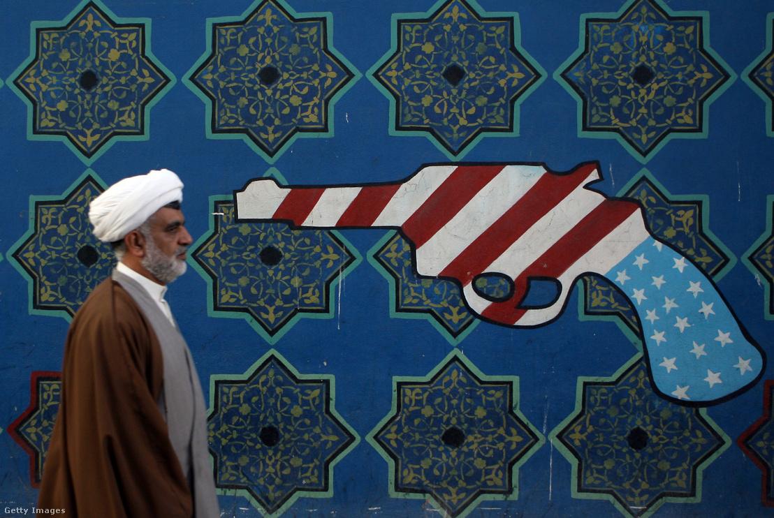 Egy iráni pap sétál el a teheráni amerikai nagykövetség falán található festmény előtt 2007. február 22-én. Egy héttel korábban számolt be a média, hogy az Amerikai Egyesült Államok lehetséges bombázást tervez Irán ellen a nukleáris fegyverprogram miatt.