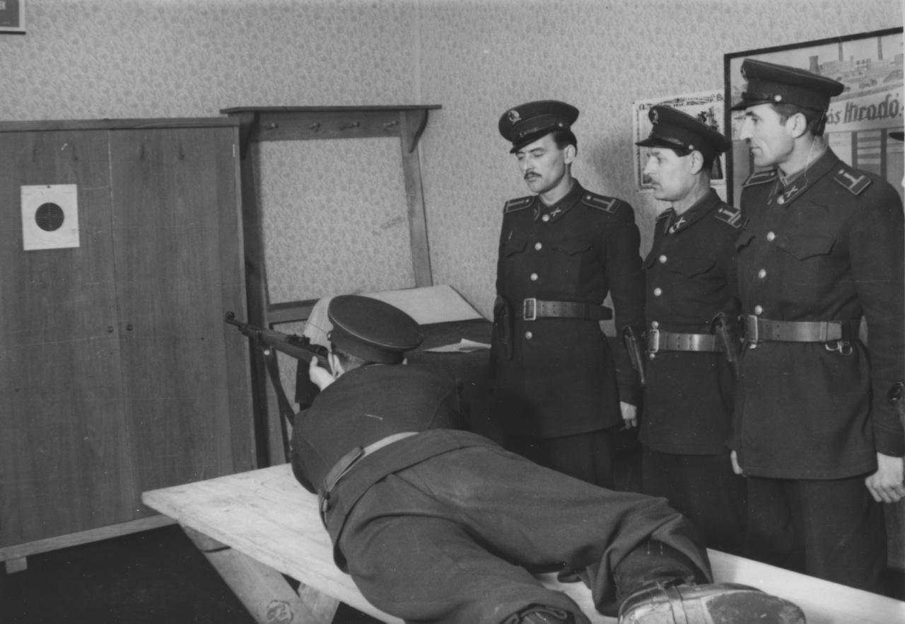 Lőgyakorlat a körletben (1951). A talán őrsparancsnokságon végrehajtott lőgyakorlat nyilván kizárólag a fénykép céljából készült, különben nem egy méterről várnák a társak az eldördülő lövést. A lőtáv önmagában is olyan nevetségesen rövid, hogy nem lehet túl komolyan venni a képet.