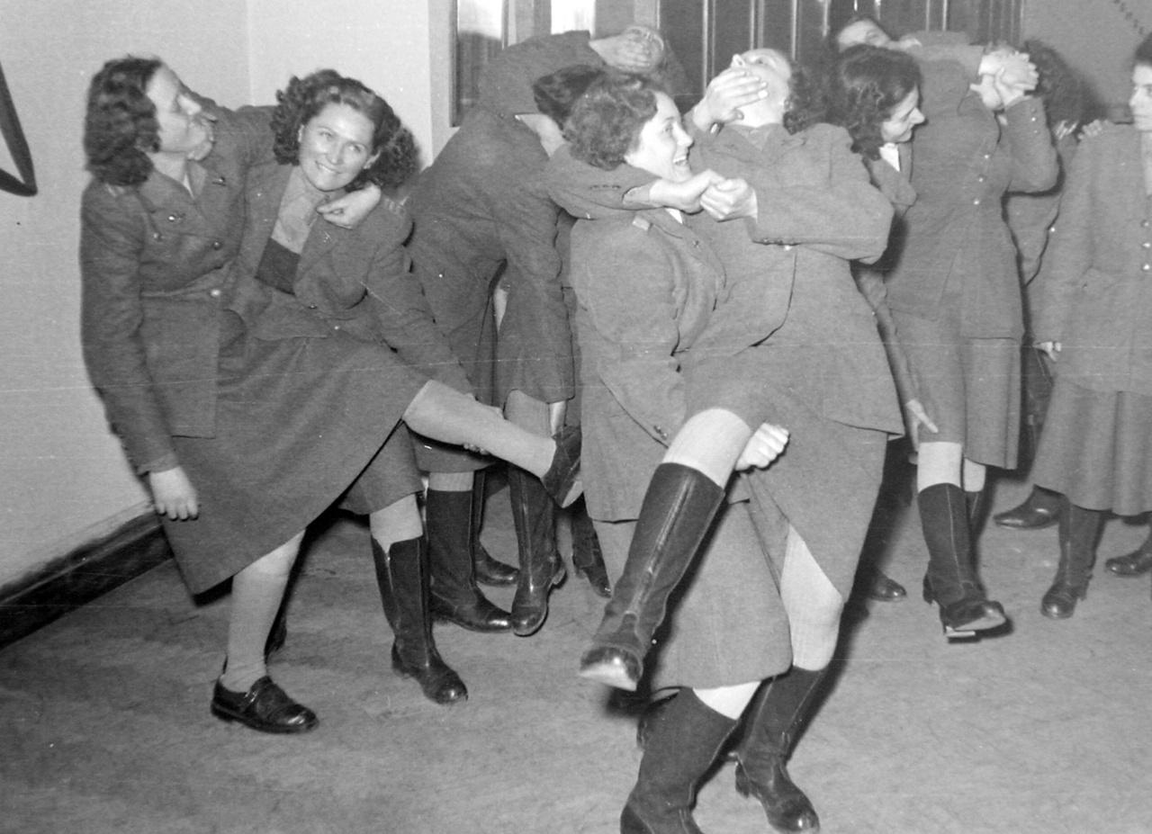 Nem táncjelenetet látunk, a nőbajtársak önvédelmi oktatáson vesznek részt. 1950-es jelenet, a női rendőrök fizikai közelharcot modellálnak, a feladata a társ térddel való kibillentése az egyensúlyából.
