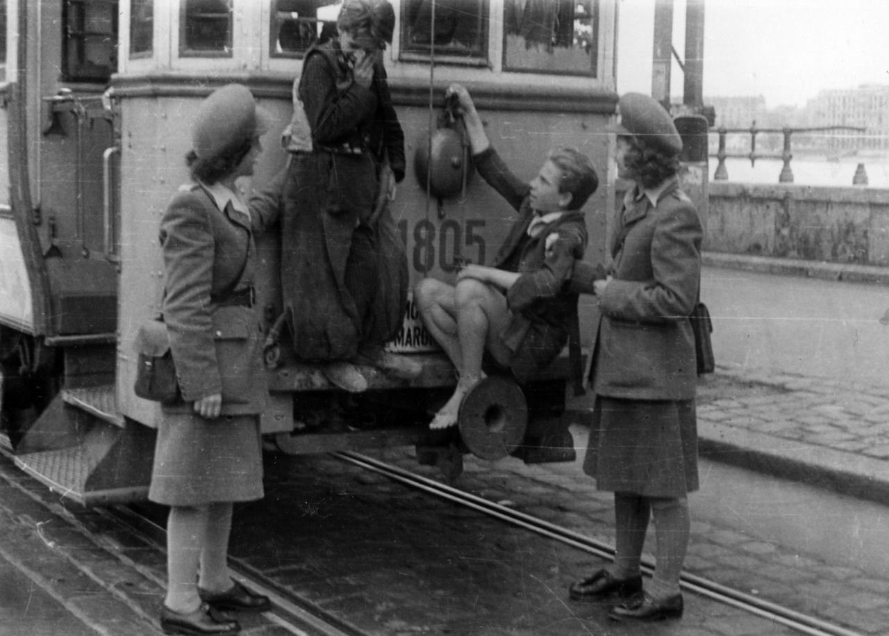 Valahol Európában, konkrétan a Margit-híd budai oldalán: tujázó fiatalok rendreutasítása. Az 1948-as intézkedés klasszikus jelenetet hoz elénk: a tujázás a második világháborútól egészen a hatvanas évek végéig a fiatal gyerekek szokásos csínytevése volt.