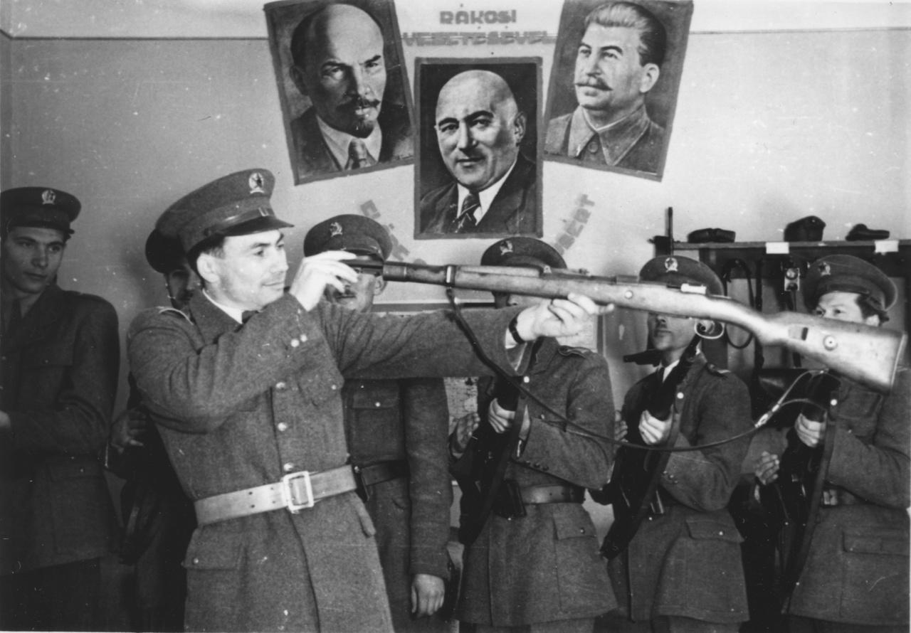 Fegyverellenőrzés a szentlőrinczi kapitányságon Zseniális, de beállított kép 1950-ből Rákosi, Lenin és Sztálin szocialista triptichonjával. A rendőr a puska irányzékát ellenőrizheti, míg a háttérben a tiszthelyettesek a dobtáras fegyverület maguk elé tartva pózolnak.