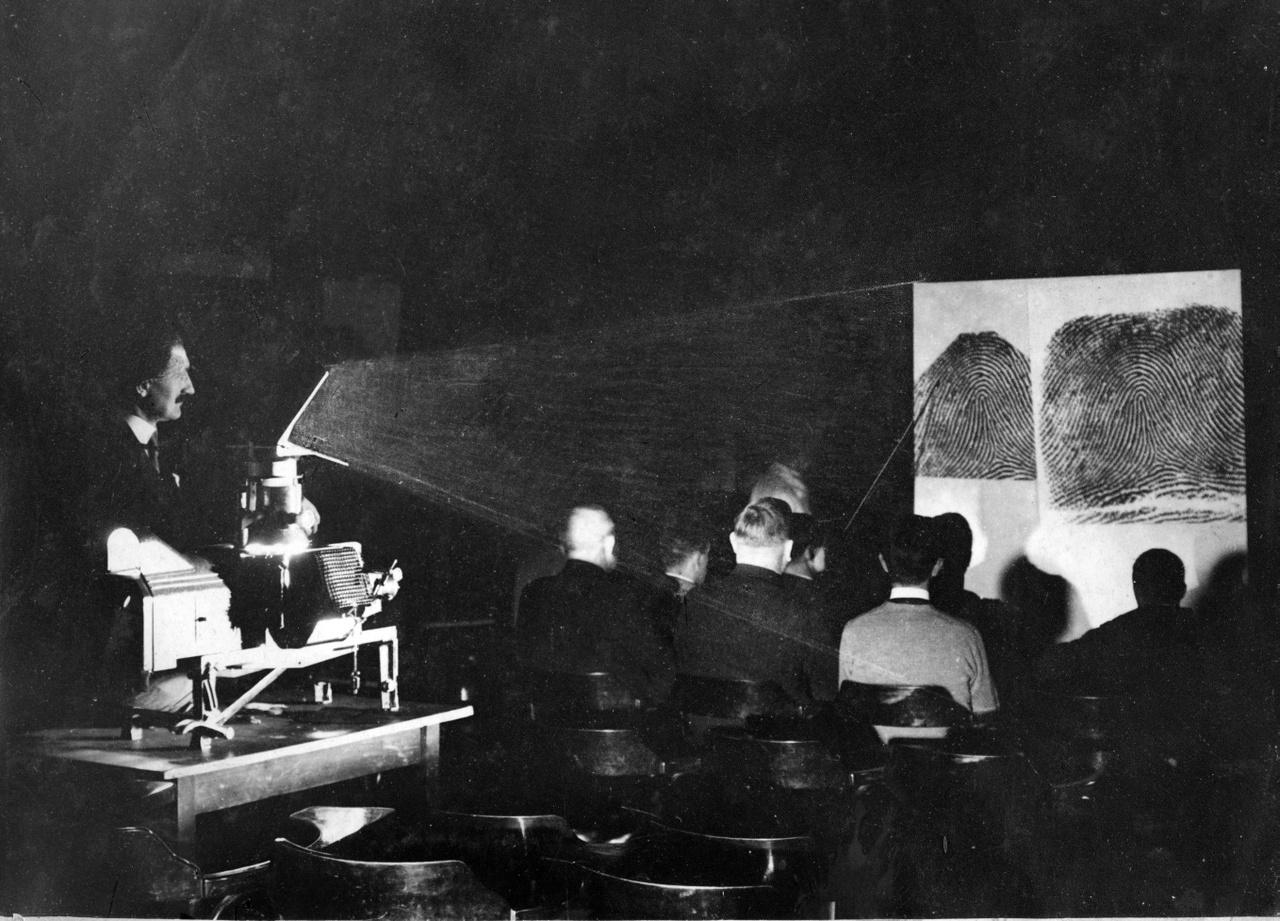 Vetítőterem a Zrínyi utcai főkapitányságon (1910). Ez az épület volt az egyik meghatározó objektuma a Horthy-rendszer fővárosi rendőrségének. A magyar kriminalisztika sokat fejlődött ekkoriban, a képen éppen egy oktatási jelenetet láthatunk. Az írásvetítő segítségével láthatólag az ujjnyomatokról volt szó, minden valószínűség szerint a képen kimerevített bőrfodorszálakról.