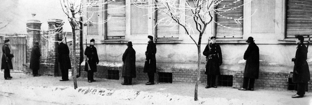 """""""Gyilkosok szuronyok között"""": a Rendőrmúzeum archívuma ezzel a képaláírással őrizte meg a datálás szerint 1920-as felvételt. A helyszín ismeretlen, egy kertvárosi részen járhatunk egy elfogáson vagy talán helyszínelésen. A három elkövetőt csendőrök veszik körbe."""