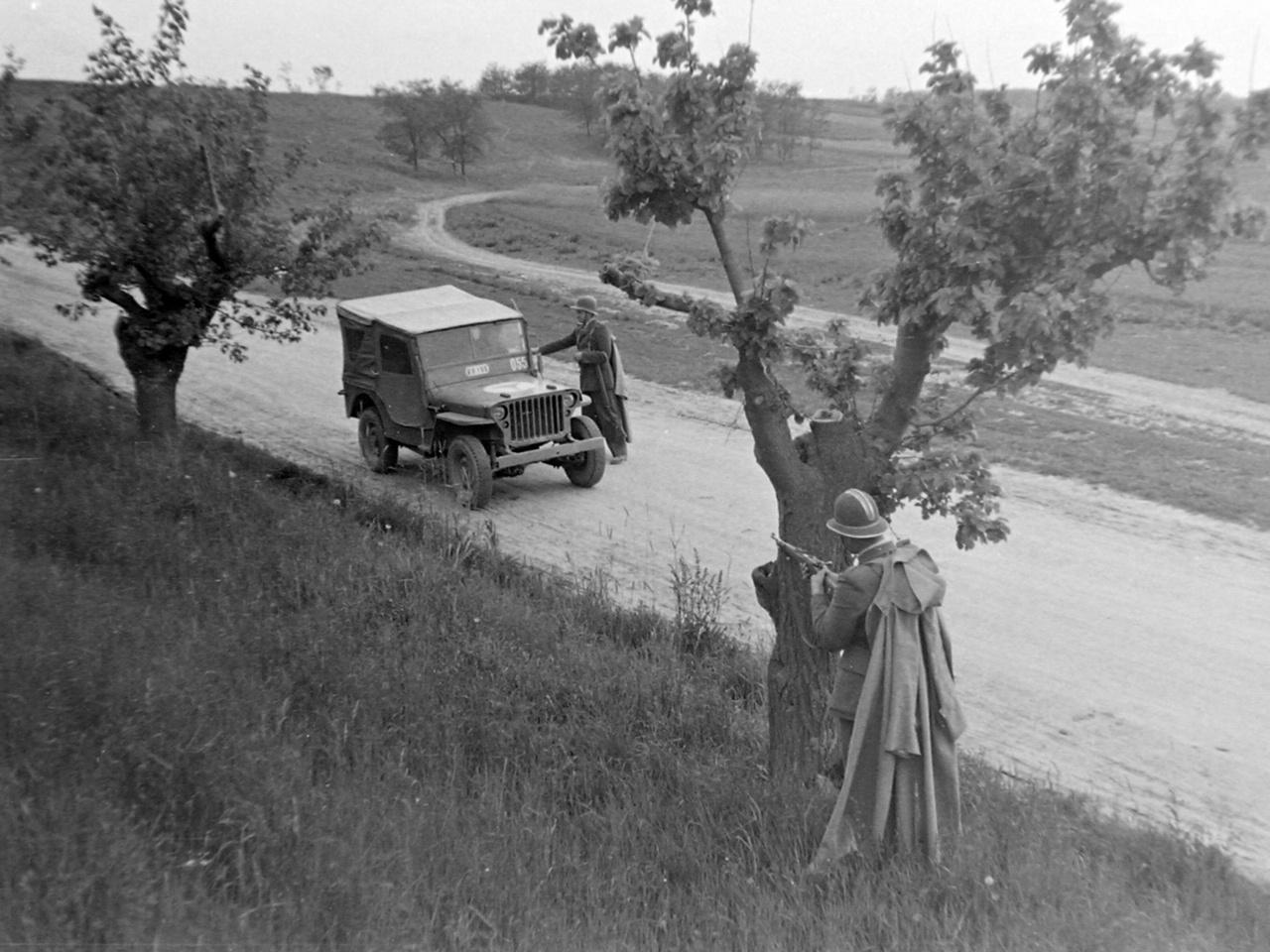Igazoltatás a határon háttérbiztosítással (1949). A kommunista hatalomátvétel után készült fotó valószínűleg beállított volt: az autó katonai jármű, benne a sofőr uniformisban ül, és valódi helyzetben egy épeszű járőr sem egy ilyen fa mögött keresne magának fedezéket,  ahol ennyire tisztán kivehető lenne egy veszélyesnek ítélt autó számára.