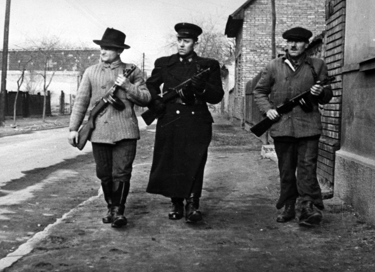 Ugrunk az időben: 1957, karhatalmi járőrözés néhány hónappal a forradalom leverése után. A dobtáras géppisztolyok közül csak a középső lehetett hivatalos állományban (a hajtókáján lévő rendfokozati jelzés szerint talán őrnagyi rangban), a két szélső önkéntes rendőr lehetett.