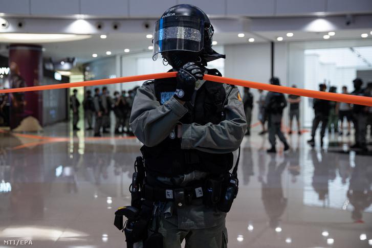 Rohamrendőr áll az új nemzetbiztonsági törvény ellen tüntetők előtt egy hongkongi bevásárlóközpontban 2020. július 6-án. A hongkongi demokráciapárti tüntetők szerint a július 1-jén hatályba lépett törvény korlátozza a szabadságjogokat, betiltja a lázadást, az elszakadási törekvések hangoztatását, és a kínai központi kormányzat ellen irányuló cselekvéseket.