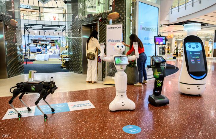 5G robotok fogadják Bangkokban egy bevásárlóközpont látogatóit 2020. június 4-én.