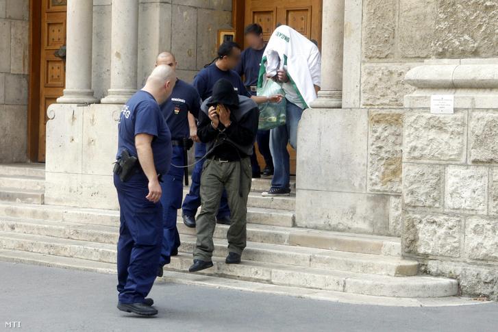 Rendőrök elvezetnek két férfit a Pesti Központi Kerületi Bíróság épületéből ahol döntöttek a gyanúsítottak előzetes letartóztatásáról 2012. július 28-án.