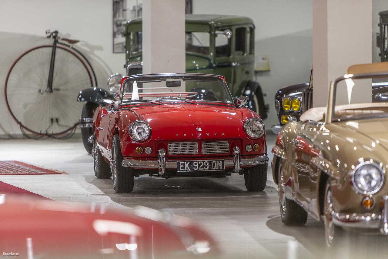 Nyitott sportautókból nincs hiány, itt rögtön egy 1965-ös Triumph Spitfire látható teljes pompájában (ami mintha a brit légiharc-sikerekről kapta volna a nevét), előtte pedig egy Mercedes-Benz 300 SL roadster feszít. (A figyelmesebbek persze rögtön észrevehették, hogy hátul, az oszlop mögött egy igazi amerikai gengszterverda, egy 1930-as Plymouth 30U bújik meg.)