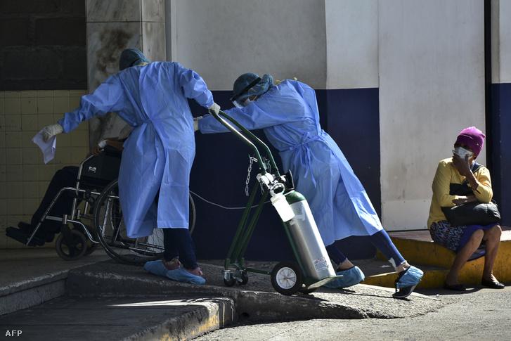 Intenzív osztályos egészségügyi dolgozók tolnak be egy koronavírussal fertőzött, kerekesszékes beteget a kórházba Honduras fővárosában 2020. július 17-én