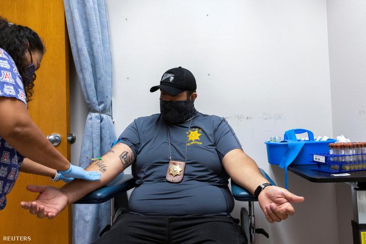 Koronavírus-ellenanyag teszthez vesznek vért egy rendőrtiszttől az Arizona állambeli Tucson Egyetemen 2020. július 10-én