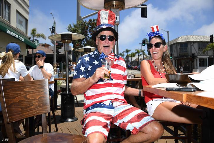 Amerikai házaspár ünnepi ebédet tart a Függetlenség Napjának alkalmából a kaliforniai Manhattan Beach egyik tengerparti éttermében 2020. július 4-én