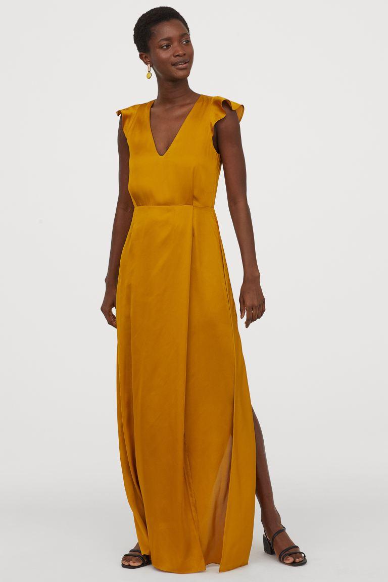 A H&M sötétsárga maxiruhája nőies és elegáns. Testhezálló derékvonala miatt karcsúsít, a magas felsliccelés pedig szexin megvillantja a lábakat. 14 995 forintért vásárolhatod meg.