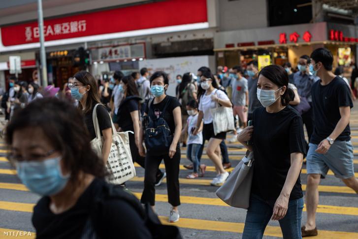 Védőmaszkot viselő járókelők Hongkong belvárosában 2020. július 27-én. A koronavírus-járvány újabb hulláma az új esetek számának gyors emelkedése miatt Hongkongban kötelezővé tették a maszk viselését a közterületeken.