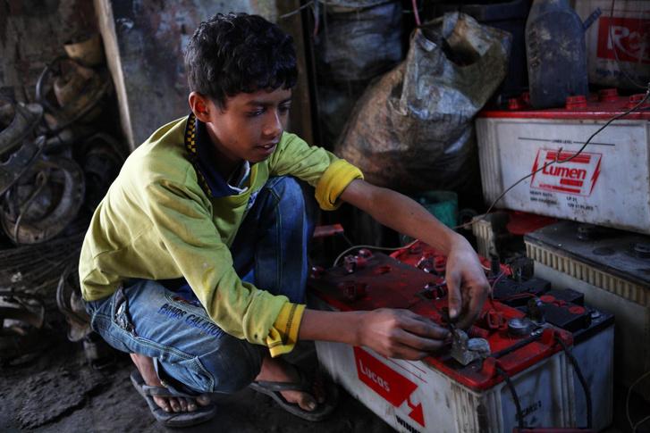Bangaldeshi gyerekmunkás akkumulátort szerel szét