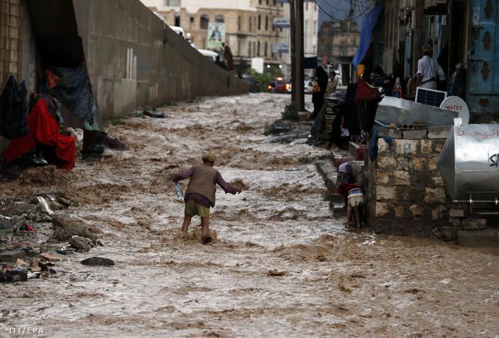 Utcán hömpölygő árvízben gyalogol egy férfi Jemenben 2020. július 29-én.