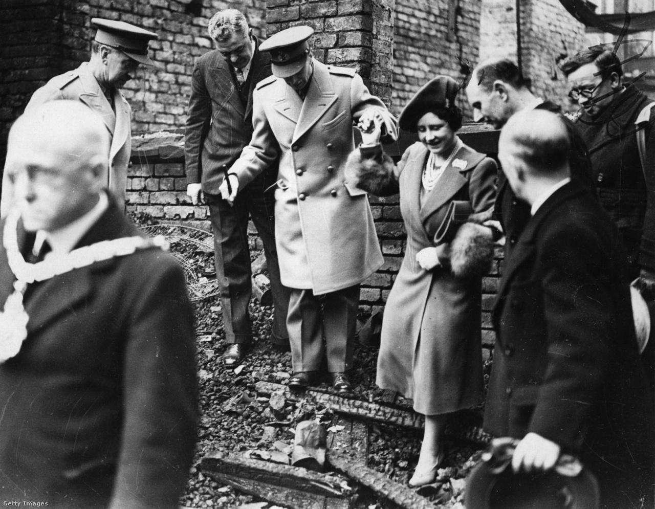 """György király és Erzsébet királyné 1941. február 14-én Salfordban megtekintik a német bombázás okozta pusztítást. A királyi pár az ellenállás szimbóluma lett, miután Hitler 1940 őszén légiháborút indított Nagy-Britannia ellen, és a Luftwaffe terrorbombázásokkal sújtotta a brit városokat. A kormány azt tanácsolta, hogy hagyják el Londont, vagy legalább a gyerekeket küldjék el a biztonságos Kanadába, de Erzsébet ezt határozottan visszautasította. """"A gyerekek nem mennek sehova nélkülem. Én nem hagyom itt a királyt. És a király soha nem távozik"""" - jelentette ki."""