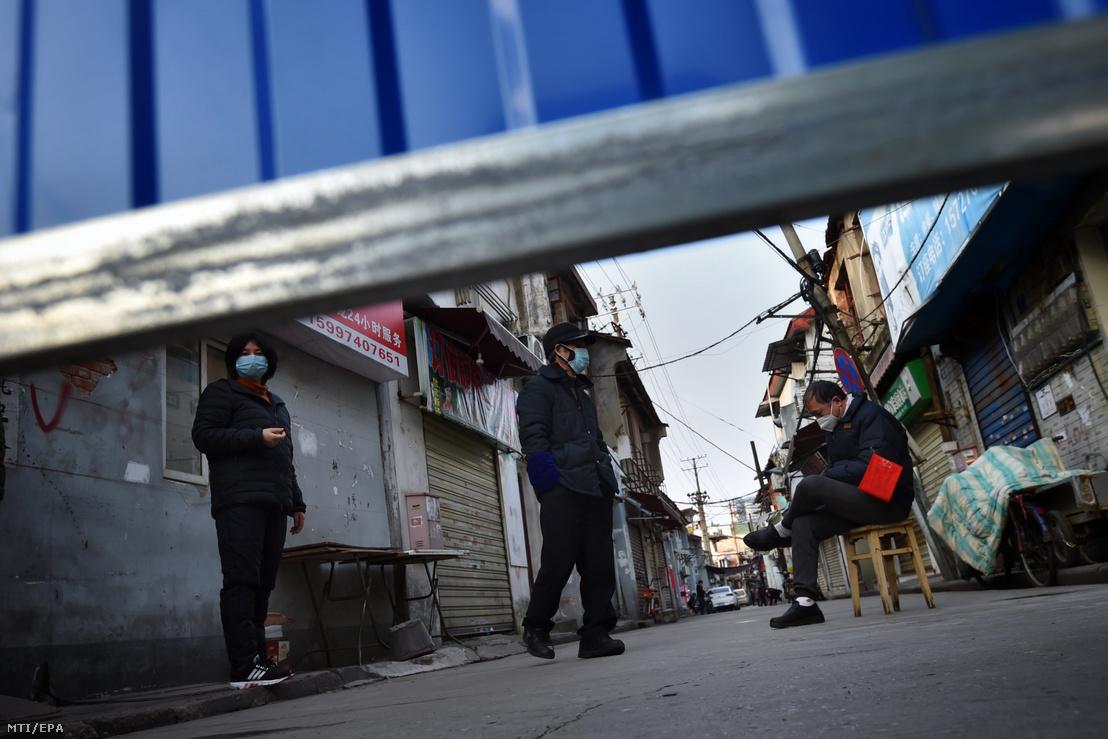 Védőmaszkot viselő emberek egy kerítéssel körülvett vuhani lakónegyedben 2020. február 23-án