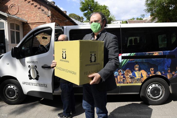 Kiss-B. Atilla Vigyázzunk egymásra! feliratú dobozban viszi az Operettszínház által készített arcmaszkokat