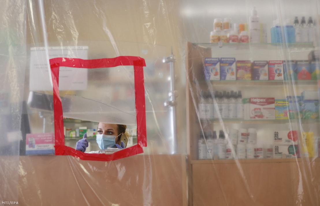Eladó egy gyógyszertárban ahol műanyag fóliával védik az alkalmazottakat az ukrajnai Bucsában