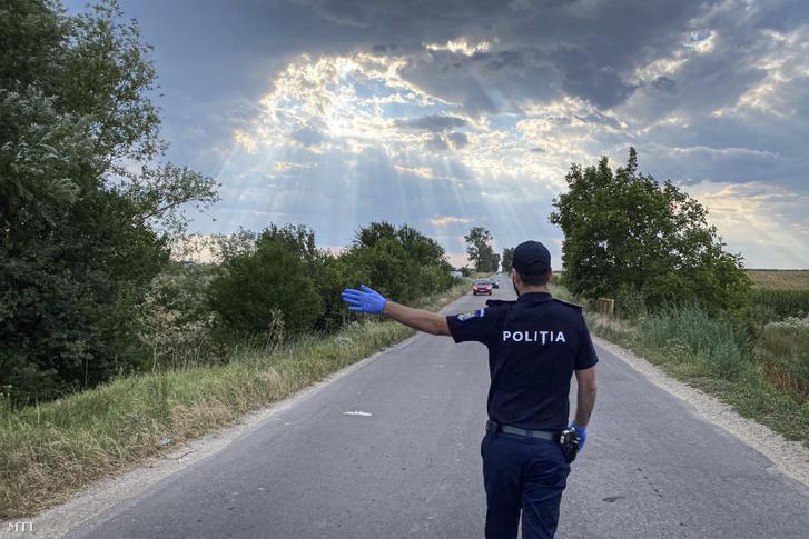 Megállítja az autókat egy rendőr a romániai Cartojani határában 2020. július 22-én miután a falut a koronavírus-fertőzöttek nagy száma miatt vesztegzár alá vonták.