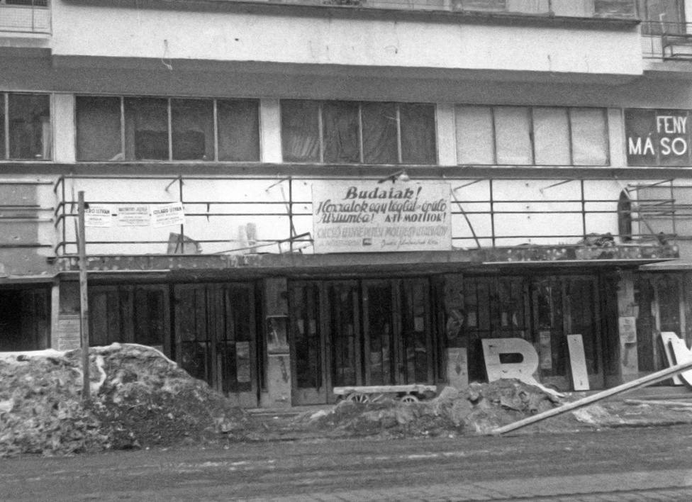 """Budán a háború előtt sem volt sok szórakozóhely, vagy színház. Ezért is volt fontos, hogy az Atriumot minél előbb felújítsák, és legalább egy film kedvéért ne kelljen átmenni a Duna másik partjára. """"Budaiak! Hozzatok egy téglát az épülő Atriumba! A ti mozitok!"""" - felirat a romos Átrium mozi homlokzatán 1947-ben."""