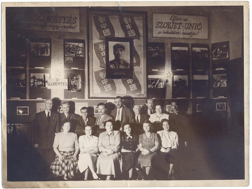 A kollektíva Sztálint dicsőítő szászló előtt pózol, körben a győzedelmes újjáépítés képei.
